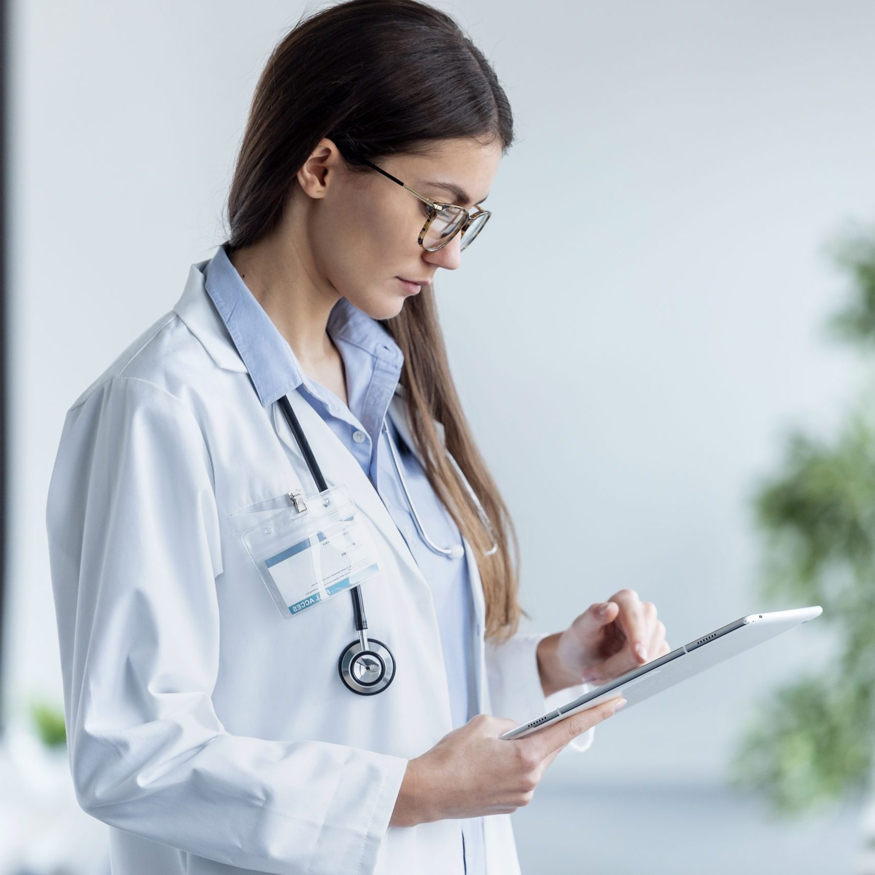 Shot of female doctor using her digital tablet while standing in the consultation.